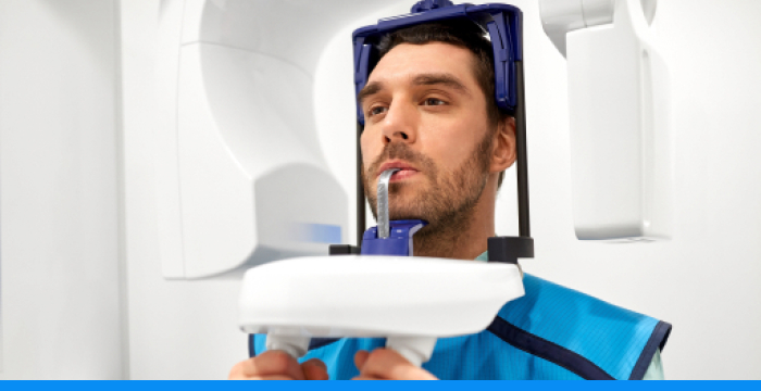 A man with his head in a CBCT scanner